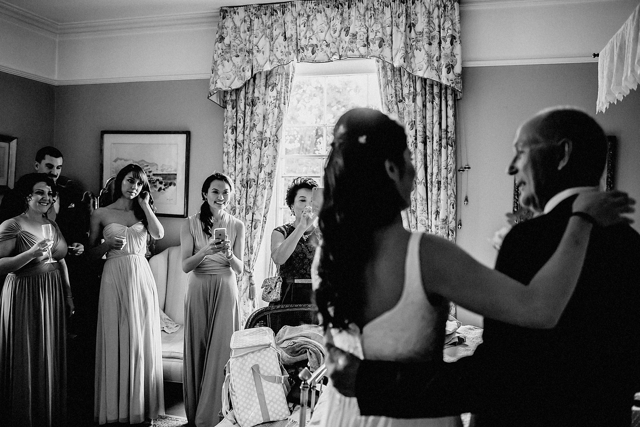 bride and dad with bridesmaids watching