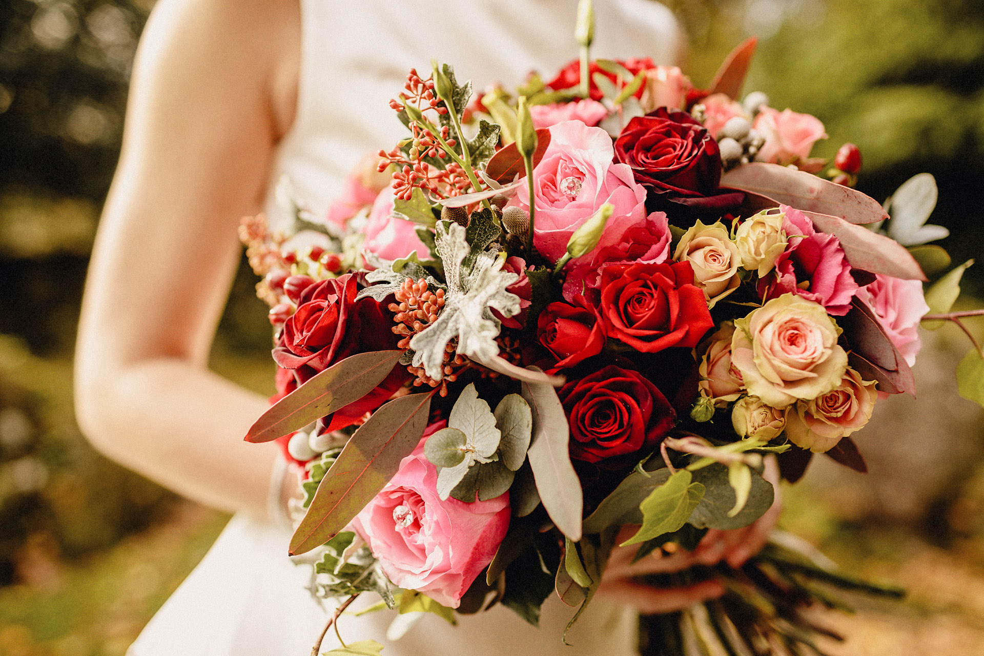 photograph of red floral boquet held by the bride